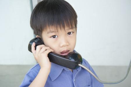 niños platicando: Niño con la vieja cabina de teléfono público