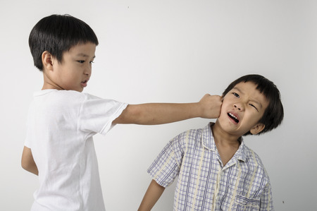 Two boys fighting by punch on to the face