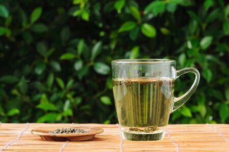 Hot herb tea in transparent glass on grass mat