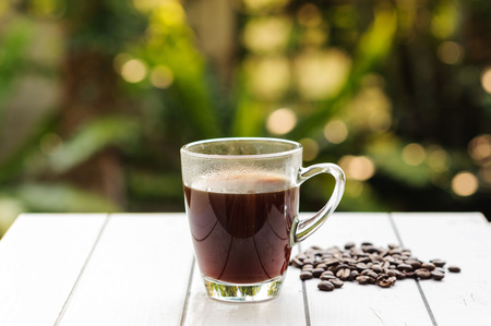 Black coffee in tranparent cup and bean on white tile Stock Photo - 37048027