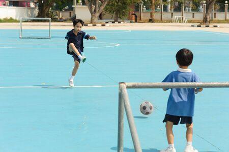 shiny floor: Boy play football on the blue floor in a shiny day Stock Photo