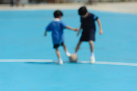 out of focus: Out focus boy play football on blue floor in a shiny day Archivio Fotografico