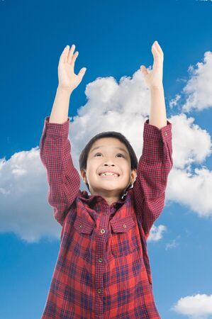 raise: Boy raise hand up to the blue sky and cloud Stock Photo