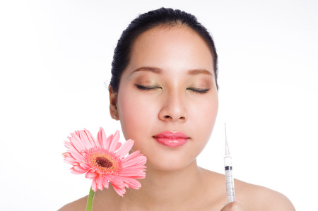 Beautiful young woman with syringe botox and flower on white background photo