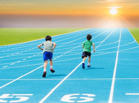 Boy running on racetrack in the statium photo