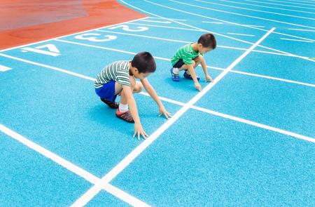 racetrack: Boy ready to start running on racetrack in the statdium Stock Photo