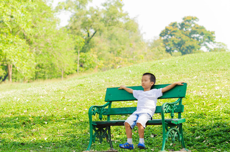 Boy sit and relax on the cair in the park