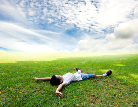 by feel: Asian Boy lay on the grass feel relax