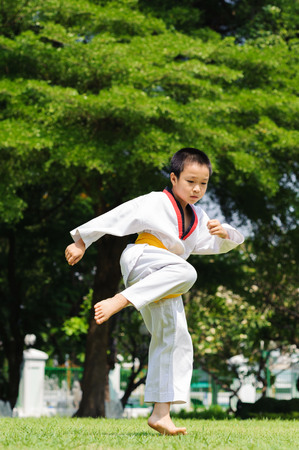 during the day: Boy practice taekwondo in the park during day