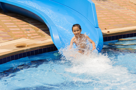 Boy play blue slider into the pool Stock Photo