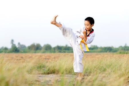 フィールド上のアジアの少年練習テコンドー 写真素材