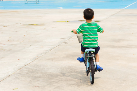 Boy rid bicycle on concrete floor on the day