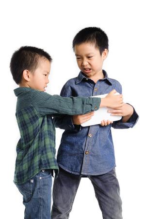 두 소년 잡고 흰색 배경에 태블릿 장치를 얻기 위해 경쟁