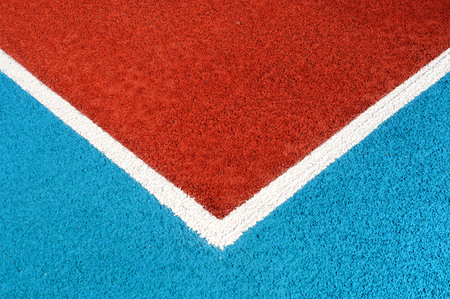 granule: Running track made from red and blue granule rubber and white corner Stock Photo