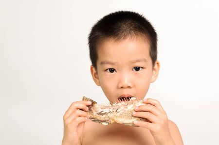 Young asian boy eating fish showing bone on white background