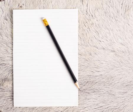 white fur: L�piz y paginaci�n rasgada apagado del cuaderno en la piel de la vaca de piel blanca Foto de archivo