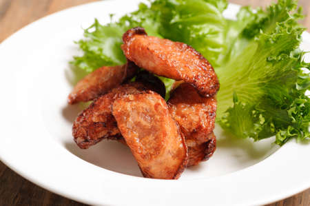 deep fry: Thai food deep fry fish sausage with vegetable on white dish on wood table