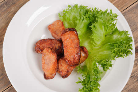 deep fry: Thai food deep fry fish sausage with vegetable on white dish on wood table