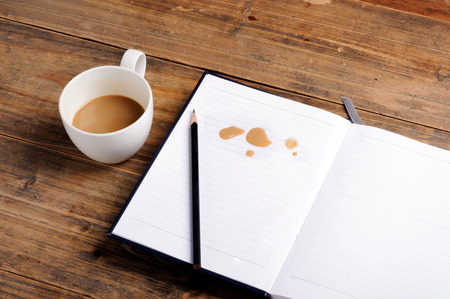 coffee stain: Coffee in cup drop on the white page notebook and pencil Stock Photo