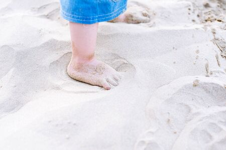 kid's day: Little kid foot step on white sand beach