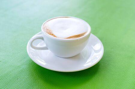 cappuccino foam: Cappuccino and milk foam in white cup on green plate