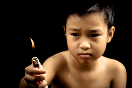 Dark tone effect Asian boy hand lighter on black background photo