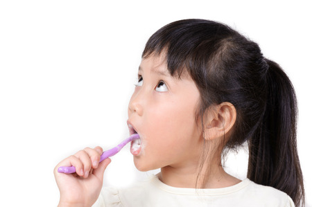 Little asian cute girl brush teeth on white background Stock Photo