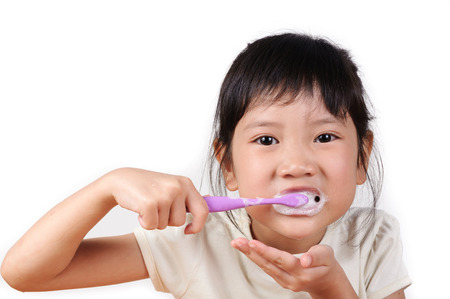 Little asian cute girl brush teeth on white background photo