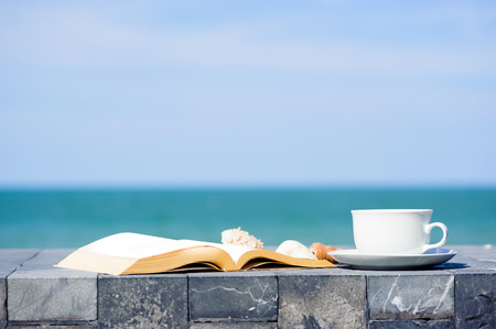 White coffee cup and old book on marble floor and sea sky background