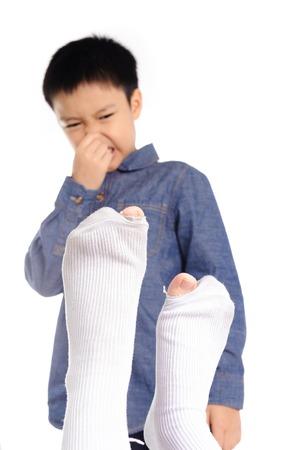 アウト フォーカスの嫌なにおいを持つ不幸な感じの少年白靴下 写真素材