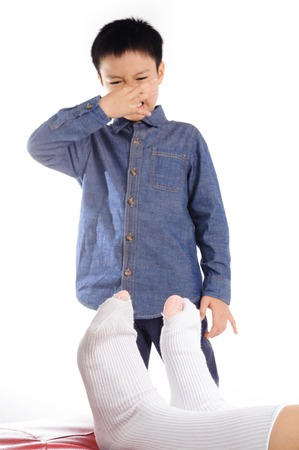 bad smell: Out focus Boy feeling unhappy with bad smell white sock