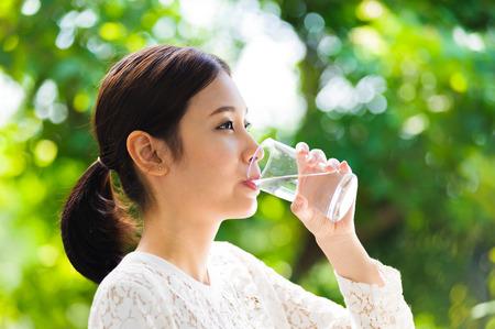 肖像画アジアの若い女の子は緑のボケ味に水を飲む 写真素材