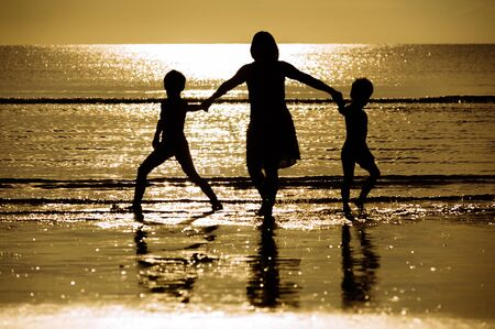 Silhouette boy mother walk on the beach and sea background photo