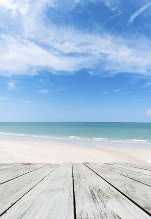 白グランジ色塗料ハード古い木製テーブル ビーチと青空に