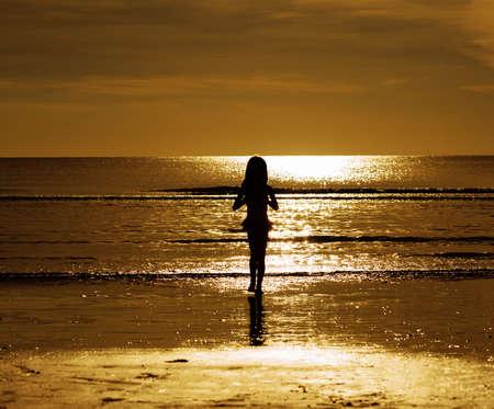 Silhouette style little girl on the beach during golden sunlight