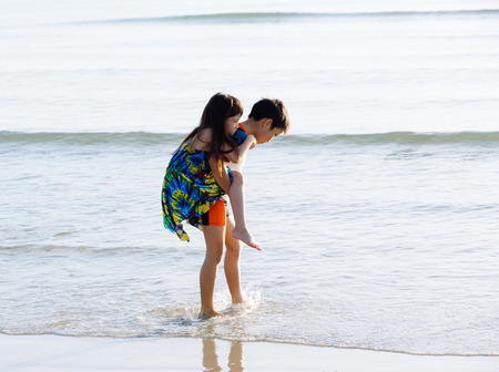sitter: Boy carry his sister at his back on the white sand beach seaside