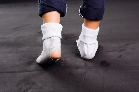 CHILD CARE: White old sock damage and hole in kind feet Stock Photo