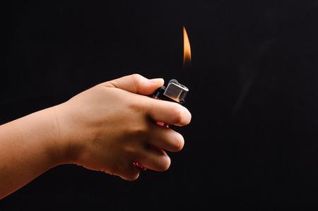 gas lighter: Asian boy hand lighter on black background