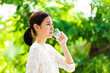 Portrait asian young girl drink water on green bokeh