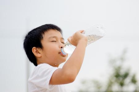 アジアの若い男の子を日光の下でスポーツの後プラスチック ボトルから新鮮な水を飲む