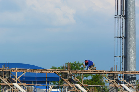 light worker: Worker without helmet construct a white building under the day light Stock Photo