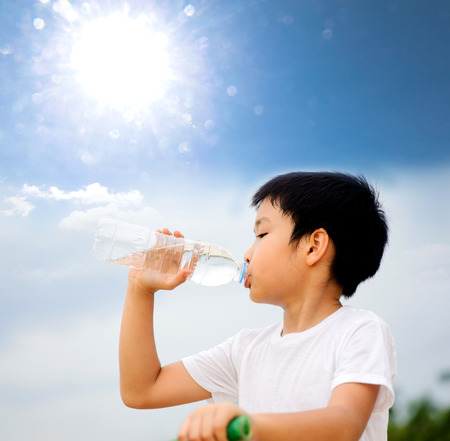 Asian young boy drinking fresh water from plastic bottle after sport against the sun Banque d'images
