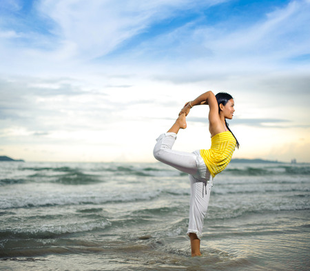 Thin focus on Young asain woman practicing yoga on the beach and during sunset