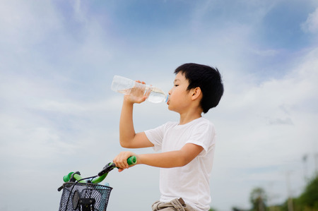 Asian young boy sit on bicycle  drinking fresh water from plastic bottle after sport in daylight Standard-Bild