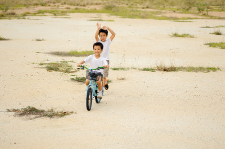 Two boy play on the dry land with a lot of dry weed in the day 版權商用圖片