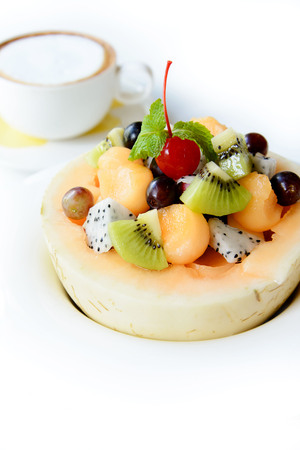 grape fruit: Mix of fresh tripical fruit salad in melon on white bowl and out focus of coffee. Stock Photo