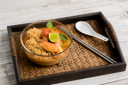 resturant: Instant noodle with Tom Yum Goong - Famous and very delicious food that hot and spicy soup with shrimp that could easily found in most of resturant in Thailand, serve in glass bowl. Thai Cuisine Stock Photo
