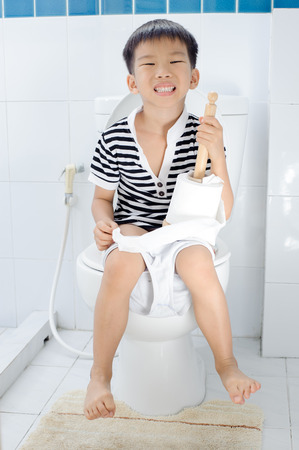 pee pee: Young Asian Boy sit on white lavatory in toilet