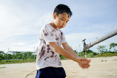 hot day: Close up Asian boy take water from old faucet on hot and dry empty land. Water shortage and drought concept.