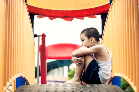 Young looks poor boy sit and wait at yellow bar playground.